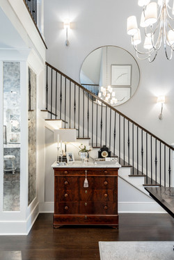 Mixing a vintage piece of furniture with modern coastal decor for an elegant look in the entryway