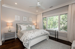 Guest bedroom with custom bedding and furnishings in neutral tones