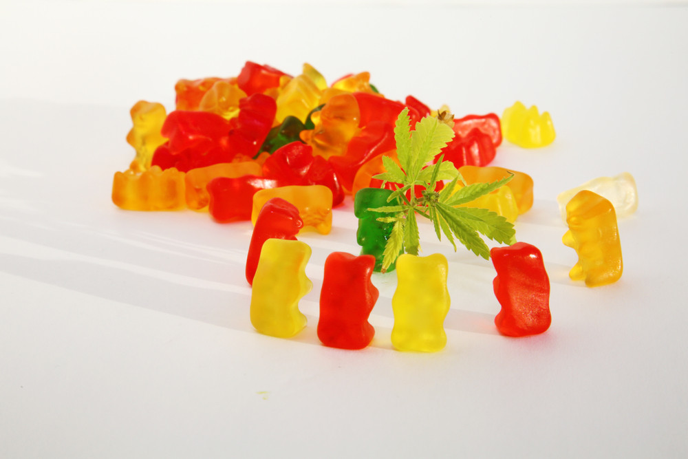 Pile of Gummy Bears with Group of Gummy Bears Surrounding a Cannabis Leaf
