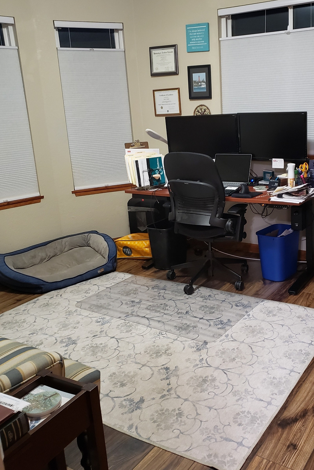 Home office showing desk with laptop and two computer monitors, desk chair, rug, dog bed, and corner of comfy chair