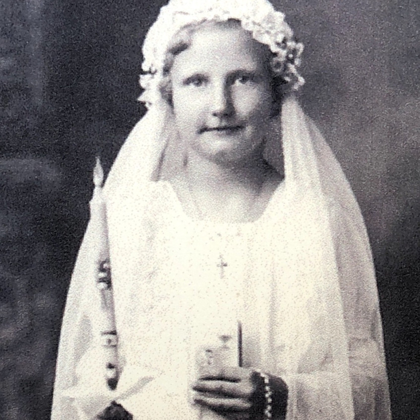Young girl in first communion dress holding candle, bible and rosary