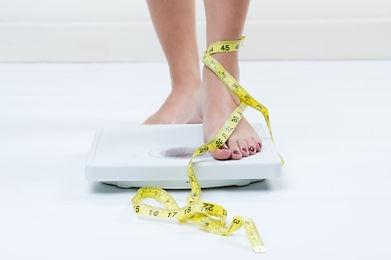 Piede femminile sulla bilancia con metro da sarti avvolto intorno alla caviglia