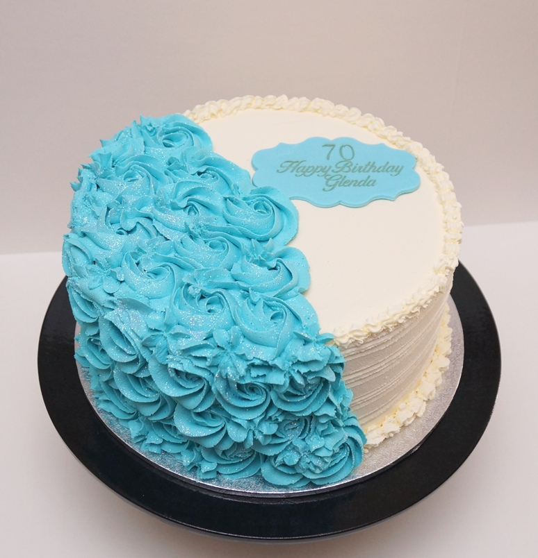 White buttercream with blue piped roses