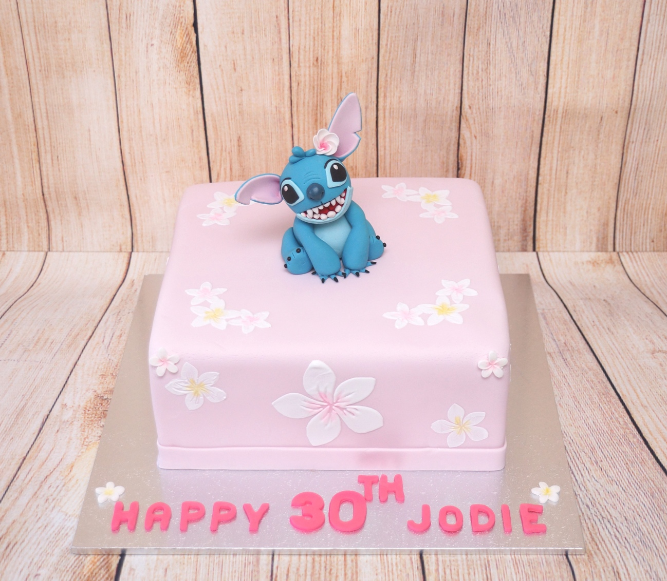 Pink cake with frangipanis and Stitch 2.