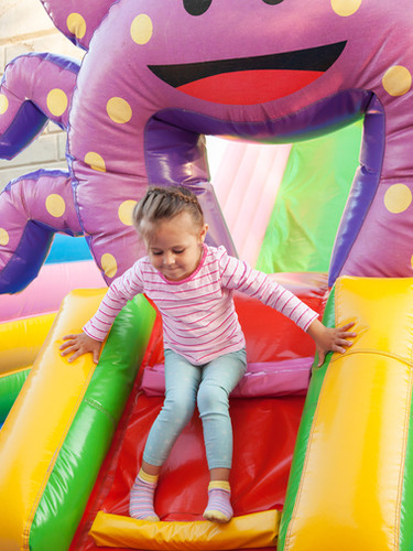 Chica jugando en el castillo hinchable