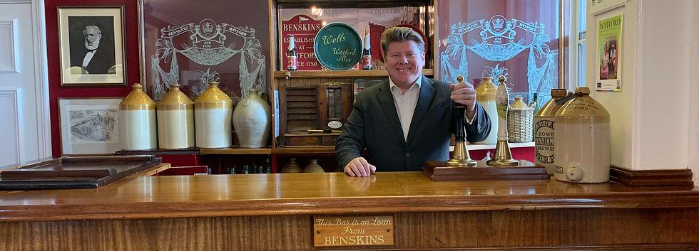 Dean Russell MP Watford pulling a pint behind a bar