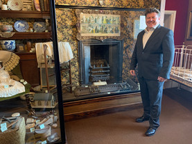 Dean Russell MP Watford standing next to a fireplace