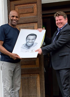 Dean Russell MP with Luther Blisset with portrait of the legendary footballer outside Watford museum