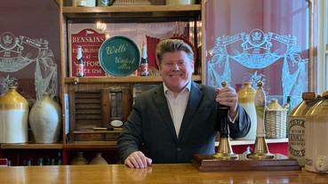 Dean Russell MP Watford pulling a pint behind a bar