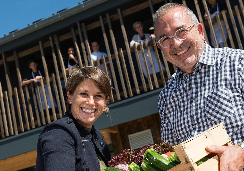 Perret Cuisine et Convivialité : L'équipe en arrière plan et Emilie et Yves Perret au premier plan