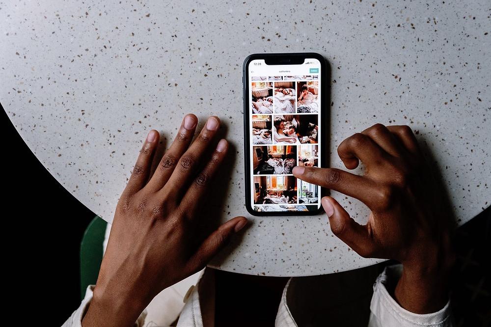 Hand scrolling through social media on phone Toronto Opiia