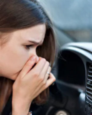 YOUNG WOMAN HOLDING HER NOSE BECAUSE OF
