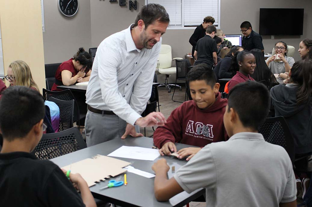 teacher works with small group of students in design thinking lab
