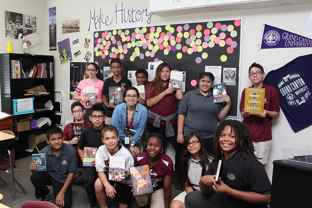 Mrs. salazar and students pose with other books purchased by donations
