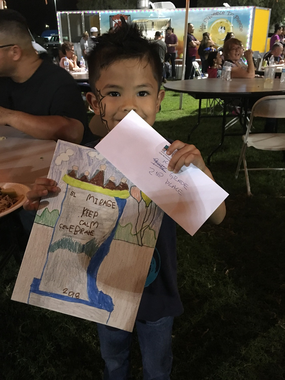 1st grader E'yan Minor holding up his 2nd place art piece