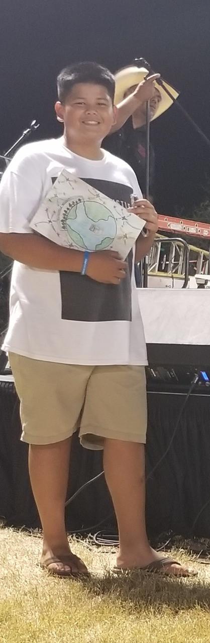 Ryan Minor holding up his winning art piece