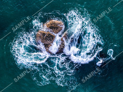 Waves Breaking Over Rock Vertical Drone Photo