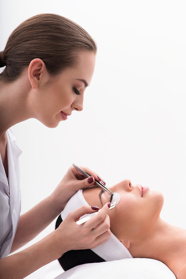 Joyful beautician lengthening female eye