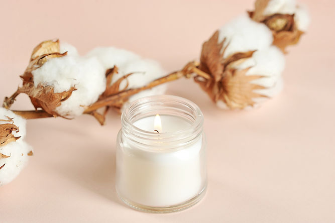 A cotton flower and a white candle in a