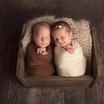Twin Newborn babies wrapped and sleeping in wooden bed