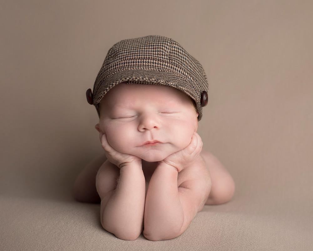 Newborn baby boy in flat cap, chin resting on hands, beautiful artwork captured by Michelle White Photography, Birmingham