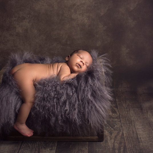 Newborn baby on fluffy bed