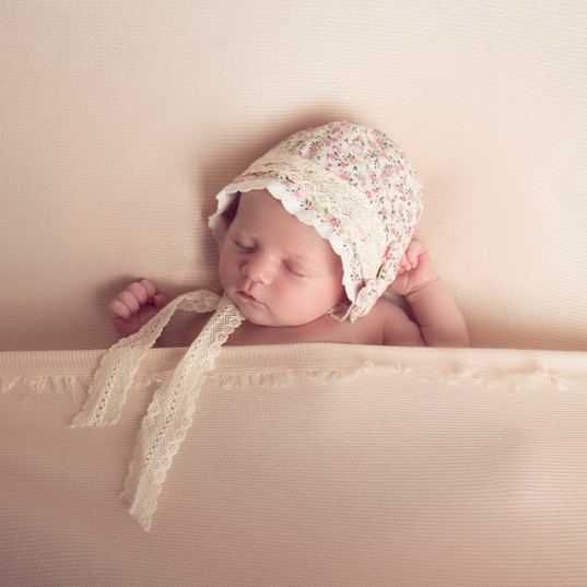 Newborn baby girl sleeping in pretty bed wearing lace hat