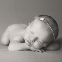 B&W newborn sleeping on hands with headband