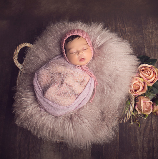 Newborn Baby on fluffy blanket in basket with flowers