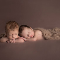 Newborn twins boys sleeping. Brown blanket and brown wrap