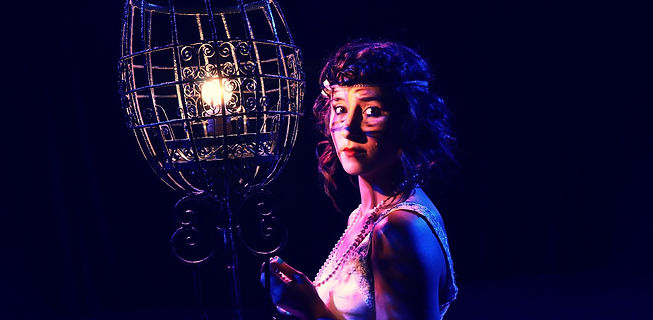 Background image for Ghost Light, one of the Ziegfeld follies holds a lamp within a cage while she stands in a dark room.