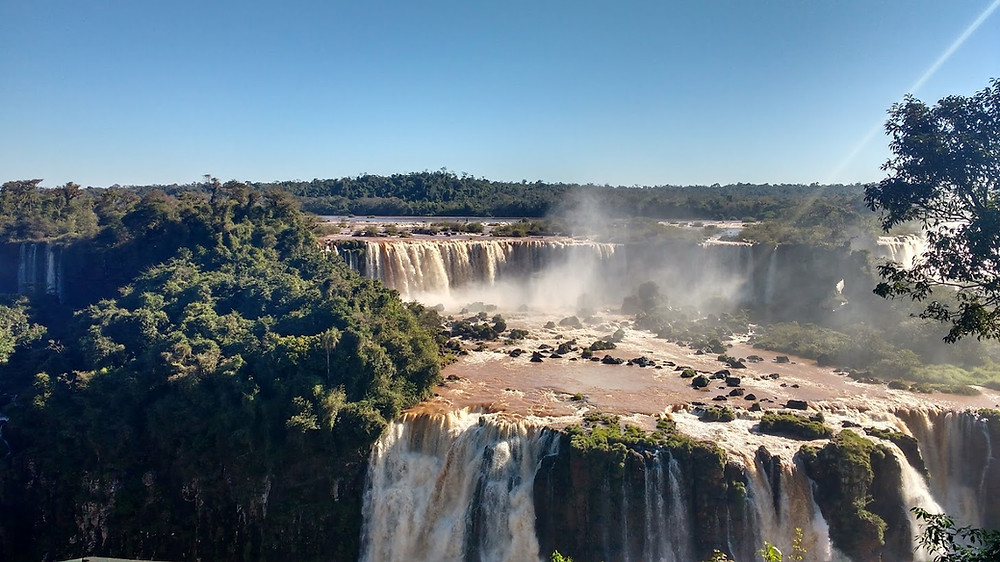 Foto da parte superior das Cataratas do Iguaçu. A foto mostra vegetação e duas grandes quedas d'águas.