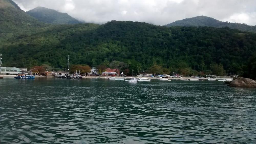 Foto da Ilha Grande. Em primeiro plano vemos um mar calmo e mais ao longe barcos de pesca atracados na areia da praia. Ao fundo montanhas cobertas por vegetação.