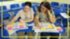 Foto de duas mulheres. Elas estão sentadas em uma sala com várias mesas e cadeiras azuis. Elas são vistas de frente e olham para papéis em cima de mesas nas quais estão apoiadas.