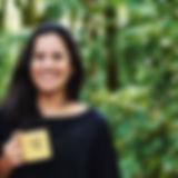 Audiodescrição: Foto de Andréia sorrindo. Ela é vista de frente do busto para cima, é morena, cabelos castanho-escuros, levemente ondulados e no comprimento do busto, tem o rosto fino e oval, sobrancelhas finas, e usa o cabelo solto. Ela tem uma pinta no canto esquerdo superior da boca. Na mão direita segura uma caneca amarela com o logo da Fubá.