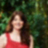 Audiodescrição: Foto de Ariane sorrindo. Ela é vista de frente do busto para cima, é branca, possui cabelos ruivos ondulados e longos e está usando uma blusa vermelha. O fundo é verde de árvores.