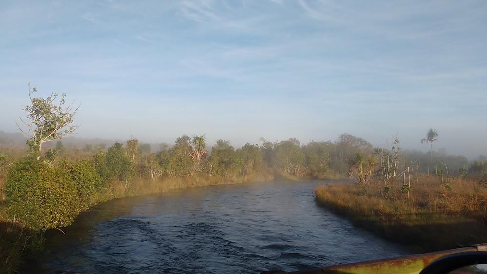 Foto da curva de um rio caudaloso e com água azul. Dos dois lados há vegetação de cerrado, com árvores pequenas, arbustos e gramíneas. Uma névoa da água do rio aparece sobre a foto.