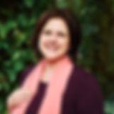 Audiodescrição: Foto de Mayla sorrindo. Ela é vista de frente do busto para cima, possui cabelo liso e curto e está usando uma blusa roxa com um lenço rosa no pescoço. O fundo é verde de árvores.