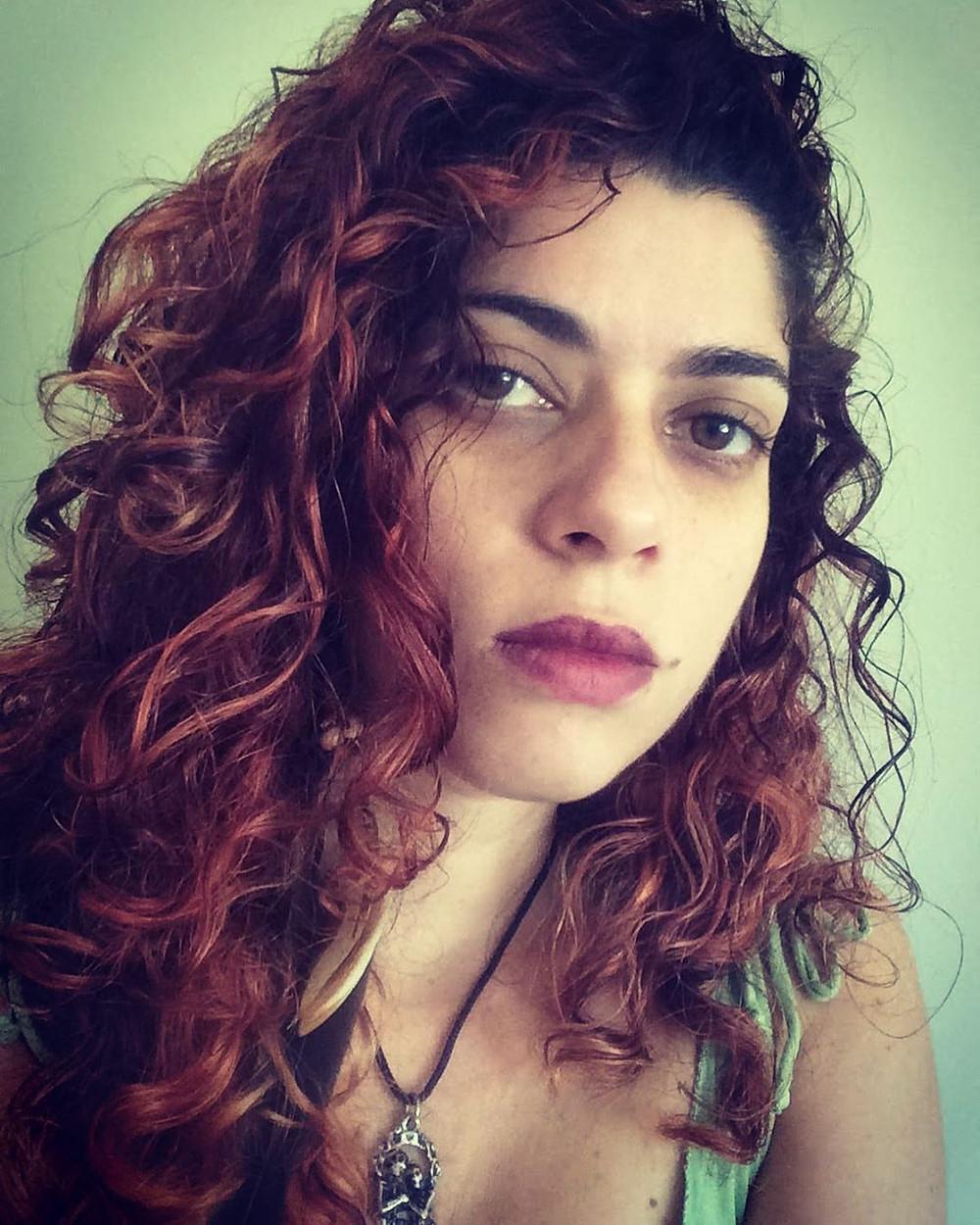 Foto de rosto da cantora lírica Patrícia Scagliusi olhando para a frente em fundo esverdeado.