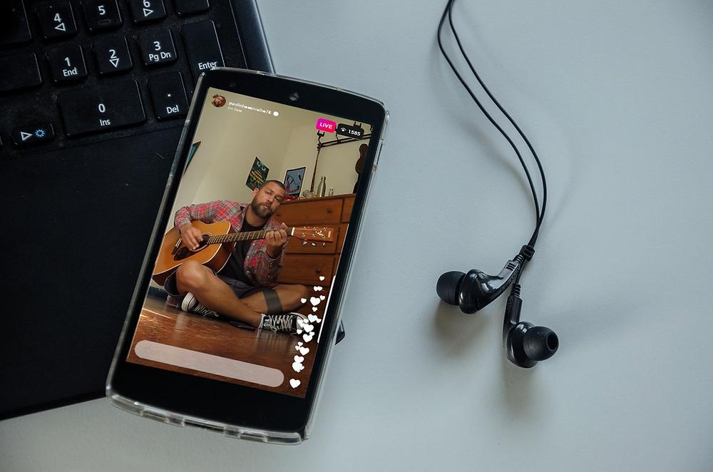 celular com foto de músico tocando violão e detalhe do fone de ouvido ao lado