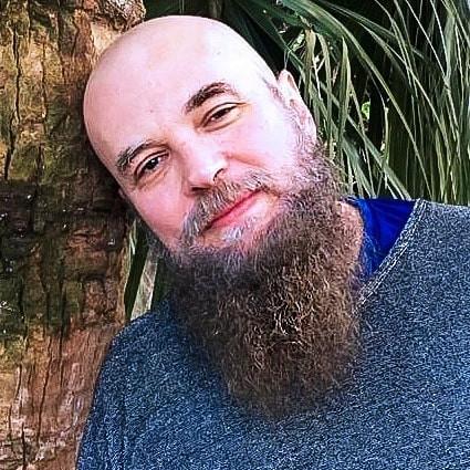 Foto do músico de MPB Oak, Foto  de rosto do artista que aparece ao ar livre encostado em um tronco de árvore.