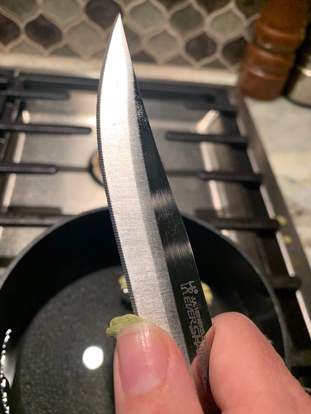 Use a sharp knife to break the cardamom pod