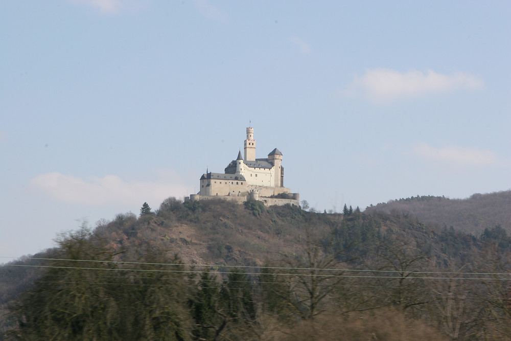 Marksburg Castle sitting high atop a mountain overlooking the Rhine River.