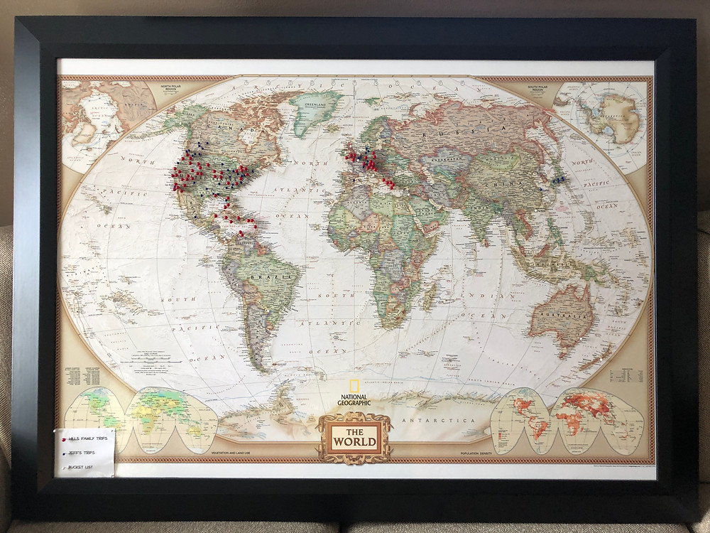 Framed world map, with blue, red or white pins placed at locations we have traveled or bucket list items we hope to travel to