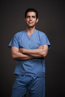Dr. Itay Wiser wearing his sergeon uniform smiling to the camera