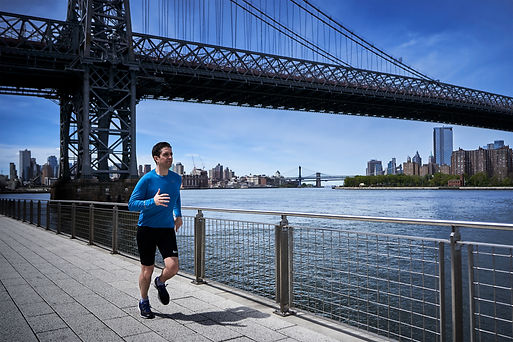 Dr. Itay Wiser running next to the Hudson river in NYC wearing sports outfit