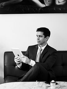 Dr. Itay Wiser wearing a suit looking on his ipad at his office