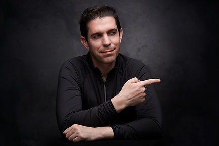 Dr. Itay Wiser in black shirt pointing with his finger right