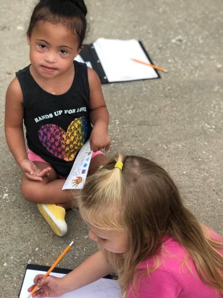 Two preschoolers enjoying taking the classroom outside.