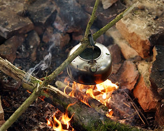 Metal kettle boiling over open fire pit